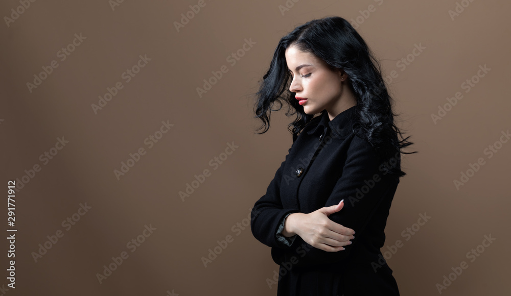 Fototapeta Beautiful young woman in a fashionable coat on a brown background