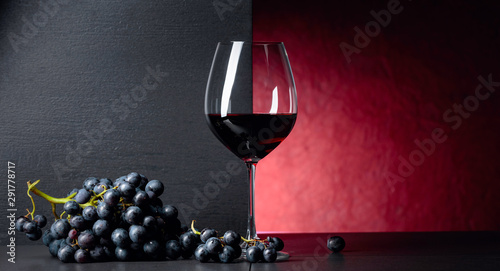 Fotografía  Red wine grapes on a black table and glass of red wine.