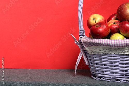 Foto auf AluDibond Rot Wicker basket with ripe juicy apples. New crop. On a coral background.