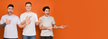 Male Friends Pointing Fingers At Copy Space On Orange Background