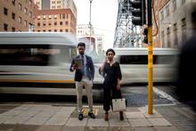 Businessman And Businesswoman Standing Beside Traffic Light