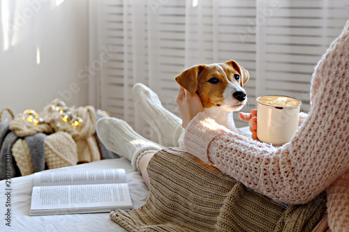 Obraz na plátně  Young woman and her adorable jack russell terrier puppy sitting on couch cozied up, covered with blanket
