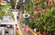 Leinwanddruck Bild - Portrait of woman florist with baskets of flowers in flower shop