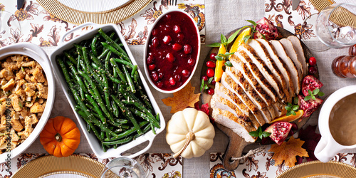 Thanksgiving dinner table with sliced turkey and sides, overhead shot - 291809768