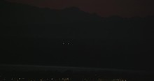 Aerial Helicopter Closeup Shot, Airplane Landing At The Tail End Of Sunset Over A Small City, Lights Twinkling, Drone Footage