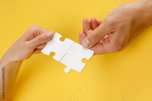 Fototapety, obrazy: cropped view of man and woman matching pieces of white puzzle on yellow background