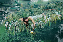 A Brunette Woman With Long Hair Lies In A Boat And Gently Touches A Water Lily Her Hand. The Princess In A White Dress Floats On The Lake. Friday, Relaxation And Enjoyment. Creative Wedding Decor