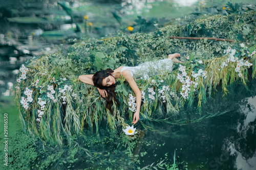 A brunette woman with long hair lies in a boat and gently touches a water lily her hand Tableau sur Toile