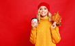 canvas print picture happy emotional cheerful girl laughing  with knitted autumn cap and Cup of coffee on colored red background.