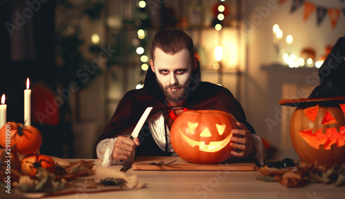 Obraz na plátně  happy Halloween!  bearded man in a Dracula vampire costume with a pumpkin in dark home
