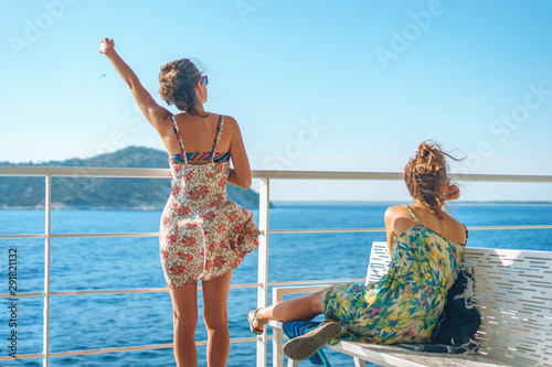 Foto Two young women girl friends sisters sitting on bench fence on deck of the ferry