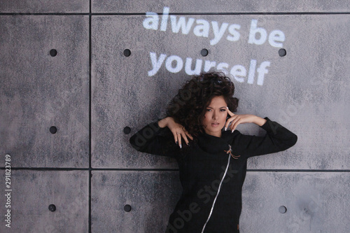 Photo Cheerful curly woman dancing on a concrete wall background