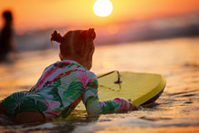 Golden Waves Of Wonderful Sea Splashing Near Adorable Girl In Swimsuit Carrying Yellow Surfboard On Sunset On An Autumn Day
