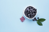 Bowl with fresh acai berries and spoon with powder on color background