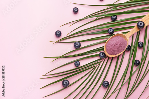 Photo Spoon with powder and fresh acai berries on color background