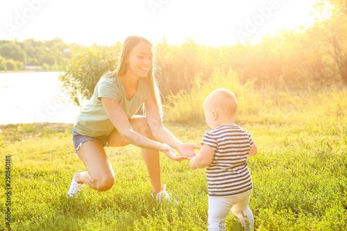 Fotografie, Obraz  Mother teaching her little baby to walk outdoors