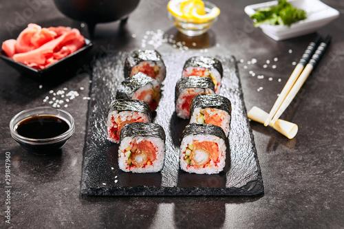 Fototapeta Macro shot of uramaki sushi roll with rice, salmon, fried shrimp, cucumber, flying fish caviar, spicy sauce and nori. Holding hot spicy sushi rolls in Japanese restaurant closeup obraz