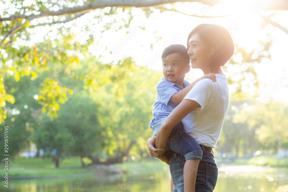 Fototapety, obrazy: Beautiful young asian mother carrying little boy in the park, asia woman happy having son and hug kid, mom love and embracing child together in summer, mother day and family concept.