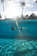 Woman Floating In Pool Water O...