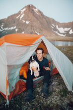Young Man In A Tent Holding His Dog In Alaskan Wilderness