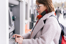 Adult Female Using ATM On Street