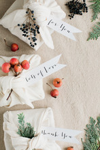 Elegant Gifts Wrapping In Neutral Colors With Linen Fabric And Botanical Elements Plus Calligraphy Handwritten Greetings Tags