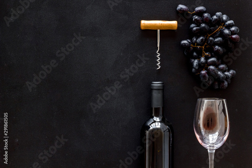 Red wine bottle near wineglass on black background top view space for text Canvas Print