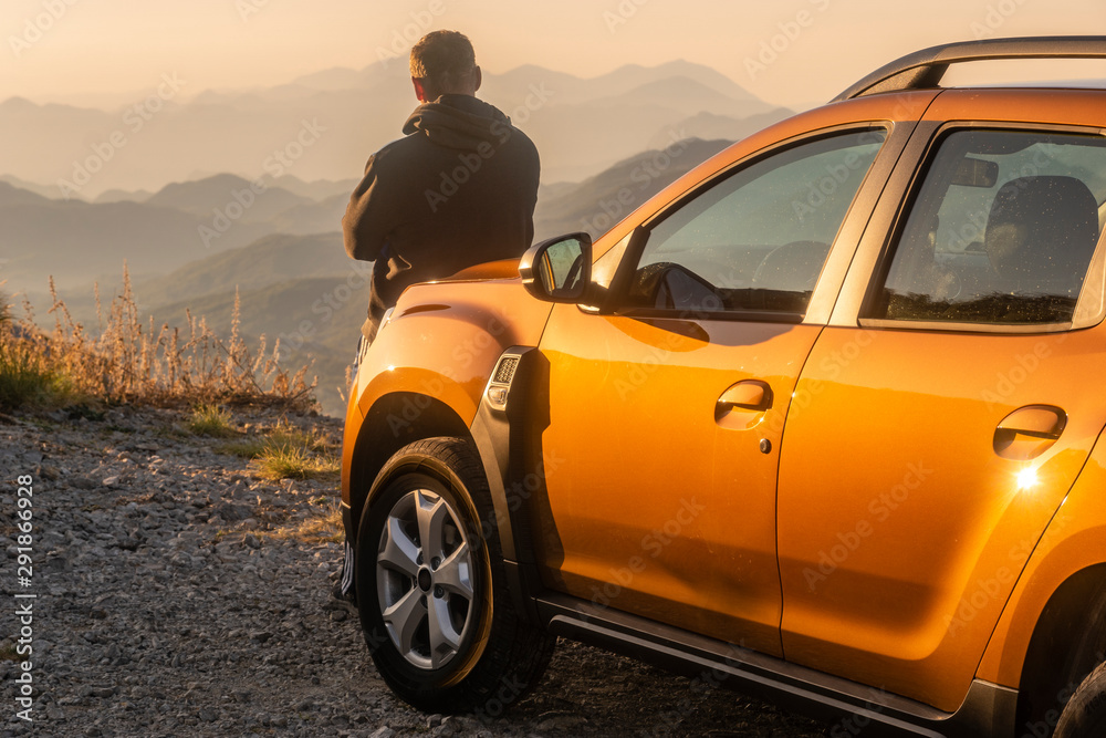 Fototapeta the driver leaning against the hood of the SUV and contemplative mountain landscape - obraz na płótnie