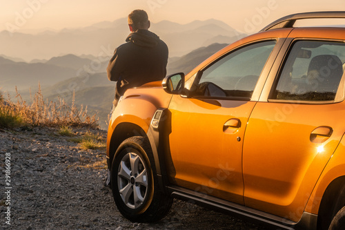 Cuadros en Lienzo  the driver leaning against the hood of the SUV and contemplative mountain landsc