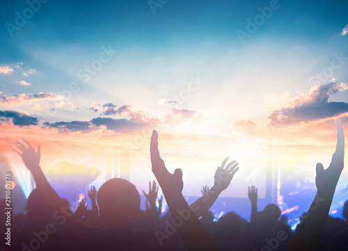 Worship and praise concept: christian people hand rising on sunset background Canvas Print