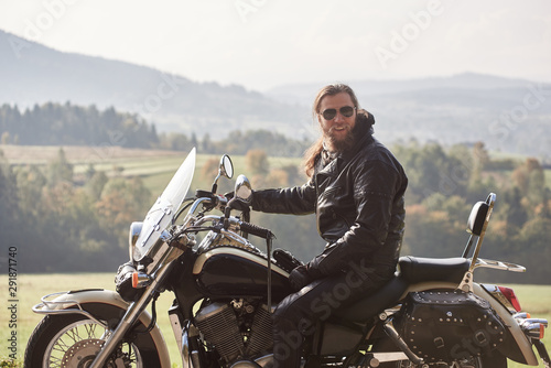 Valokuva Handsome bearded motorcyclist with long hair in black leather jacket and sunglasses sitting on cruiser motorcycle, on blurred background of green peaceful rural landscape and light foggy sky
