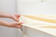 Woman's Hands Changing Light Yellow Sheet On White Mattress. Regular Bed Linen Change. Closeup. Side View.