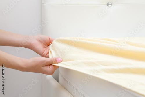 Obraz Woman's hands changing light yellow sheet on white mattress. Regular bed linen change. Closeup. Side view. - fototapety do salonu