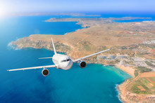 Passenger Airplane Flying Over Beautiful Blue Sea Water, Along The Coast Of The Island Beach, Summer Holiday Vacation Traveling.
