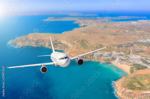 Poster Avion à Moteur Passenger airplane flying over beautiful blue sea water, along the coast of the island beach, summer holiday vacation traveling.