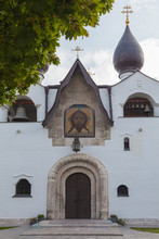 Fragment Of The Facade Of A White Stone Church With An Arched Entrance And A Black Dome. Above The Entrance Is The Face Of Jesus Christ