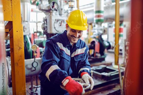 Fotografia  Smiling hardworking energy plant worker in working suit screwing valve