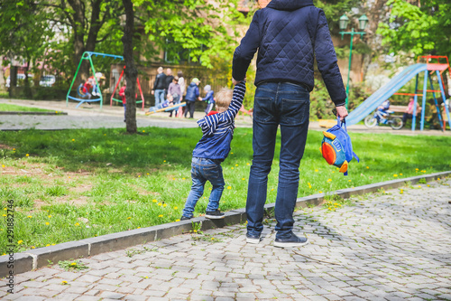Father is walking with his son on children playground. Canvas-taulu