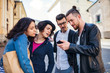 A group of young friends standing outdoor in town, using smartpone.