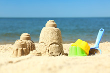 Beautiful View Of Beach With Sand Figures And Plastic Toys Near Sea