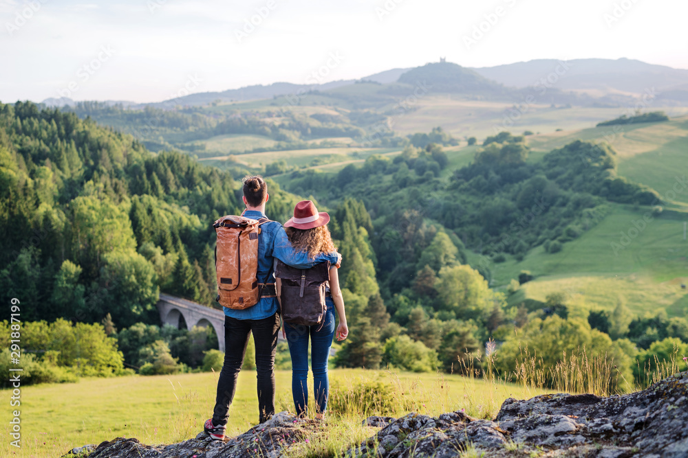 Fototapety, obrazy: Rear view of young tourist couple travellers hiking in nature, resting.