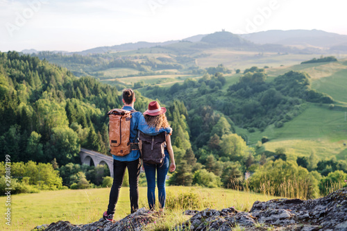 Rear view of young tourist couple travellers hiking in nature, resting.