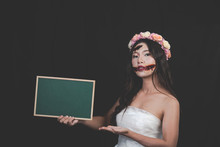 A Female Ghost Or Zombie Wearing A White Dress, Holding A Horror Green Board Halloween And Horror Concepts.