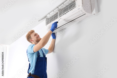 Photo Professional technician maintaining modern air conditioner indoors