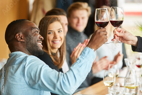 Photo Afrikanischer Mann beim Anstoßen mit Rotwein