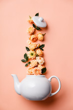 Creative Layout Made Of Whte Tea Pot With Orange Roses On Pink Background