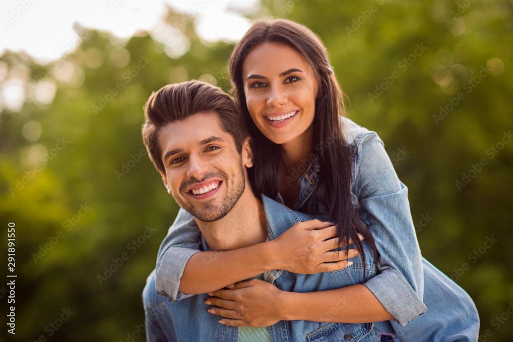 Fototapeta Close up photo of charming couple piggyback wearing denim jeans outdoors