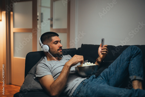 men listening music on headphones and using his smartphone, relaxed on sofa at his home - 291897340