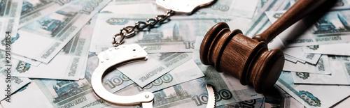 Fototapeta panoramic shot of wooden gavel near handcuffs on russian money obraz