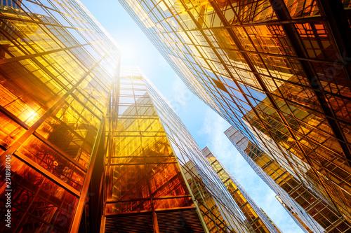 Fototapeta Skyscraper glass facades on a bright sunny day with sunbeams in the blue sky obraz